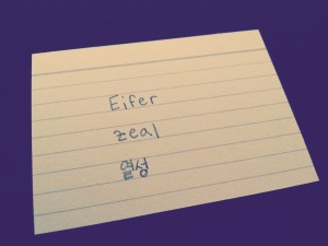 Das Wort Eifer auf Deutsch, Englisch und Koreanisch auf eine Karteikarte geschrieben. Eifer (DE), zeal (EN), 열성 [yeolseong] (KR).